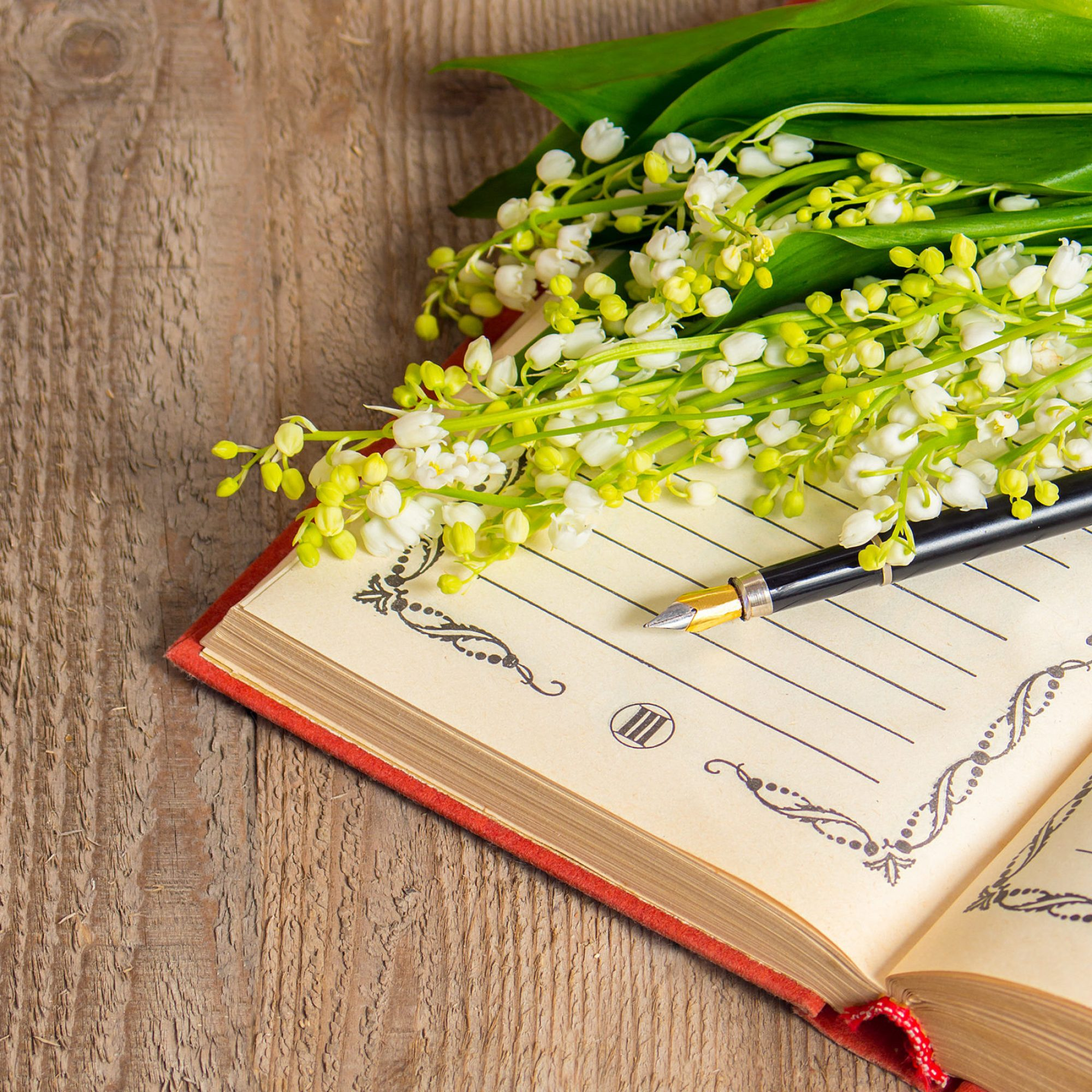 Flowers lily of the valley on the book for records and a pen on a wooden background